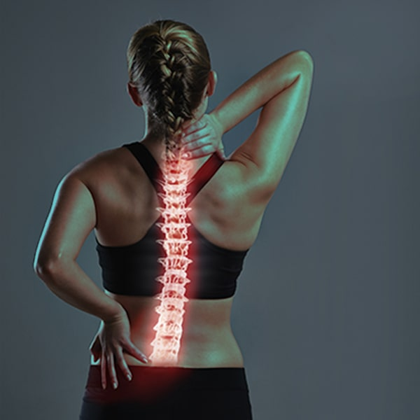 Athlete woman in pain holding massaging her back with the spinal cord highlighted - stem cells for spinal cord injury