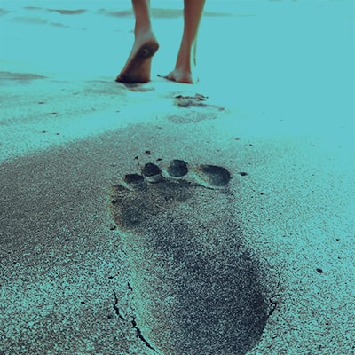 Man walking on sandy beach - stem cells for foot and ankle repair