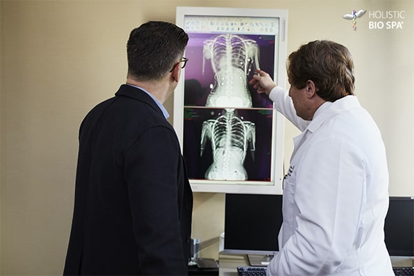 Doctor and patient examining x ray for mesenchymal sternum stem cells extraction in medical clinic in Mexico