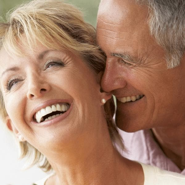 Vibrant healthy couple laughing and enjoying energy thanks to NAD therapy