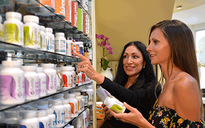 One of our health coaches with a patient browsing our health products, supplements, superfoods, and natural medicines at Holistic Bio Spa in Mexico