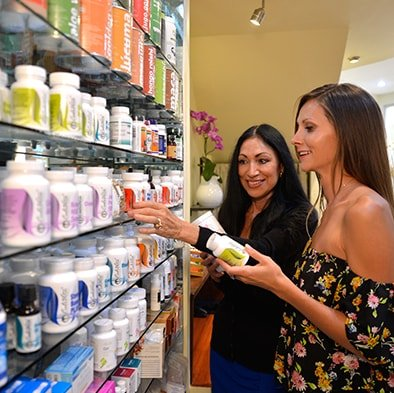 Alicia showing a patient the wide array of nutritional supplements, enzymes, and superfoods for optimal health at Holistic Bio Spa